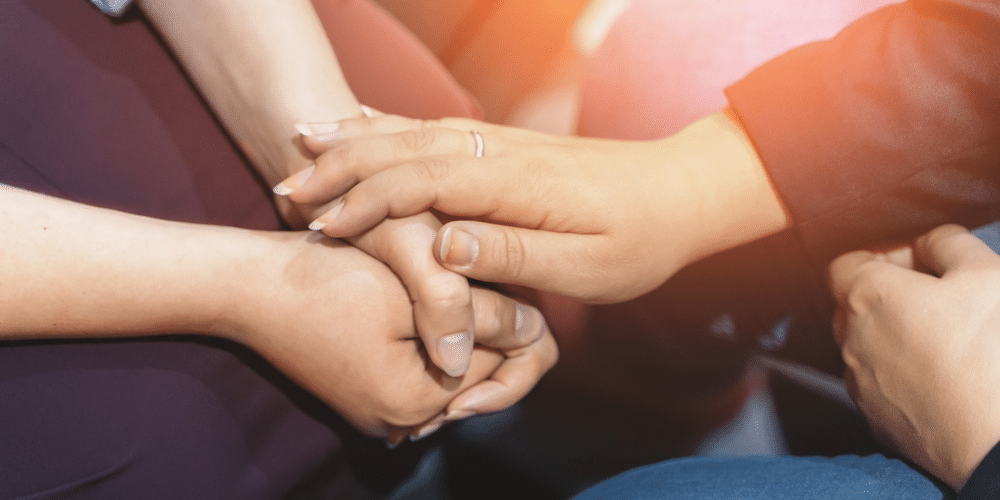 Woman's hand placed on another woman's folded hands in support